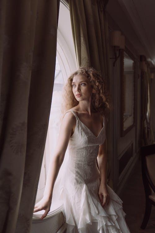 Woman in White Dress Standing Beside Window