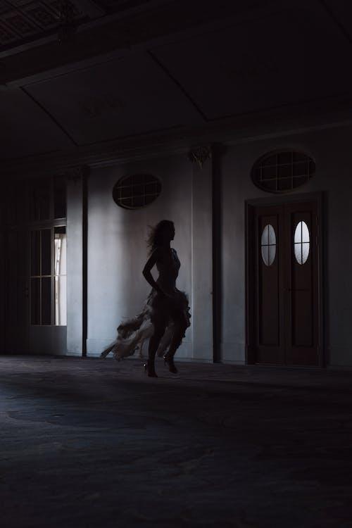 Silhouette of Woman Running on Hallway