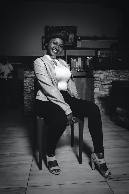Young black woman smiling brightly while sitting on chair