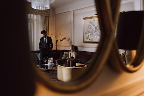 Man in Black Suit Standing in Front of Mirror