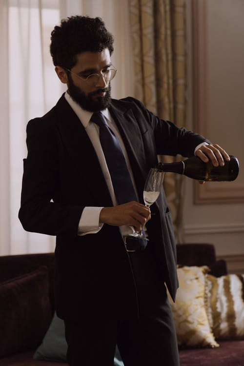 Man in Black Suit Pouring Champagne in a Glass