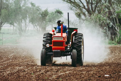 Man Riding a Red Tractor on a Field
