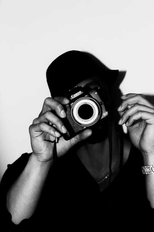 Grayscale Photo of Man Holding Camera