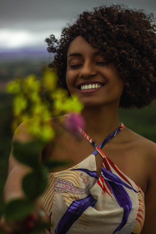 Smiling Woman in Halter Top Holding Yellow Flower