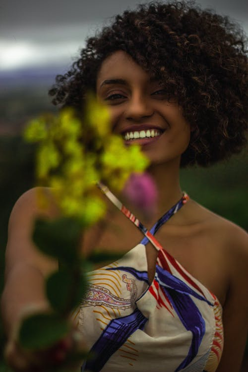 Smiling Woman in Halter Top Holding Yellow Flowers