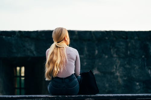 Woman in White Long Sleeve Shirt and Black Pants Sitting on Gray Concrete Wall