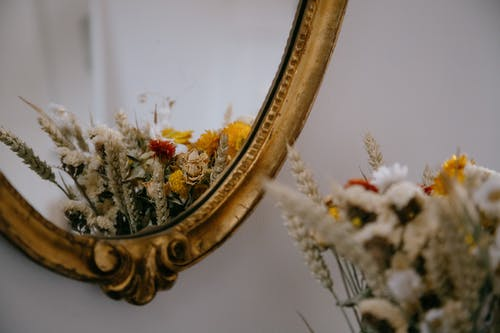 Through decorated mirror of bunch blooming flowers with dry herbs on surface near white wall