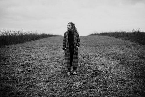 Black and white of young curly haired female in checkered coat standing in field and looking away