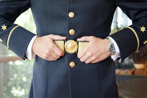 Person in Black and White Long Sleeve Shirt Holding Gold Round Analog Watch