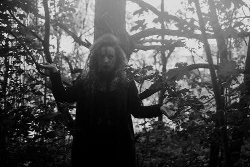 Black and white of serious female with scary face art standing in mysterious forest and looking at camera