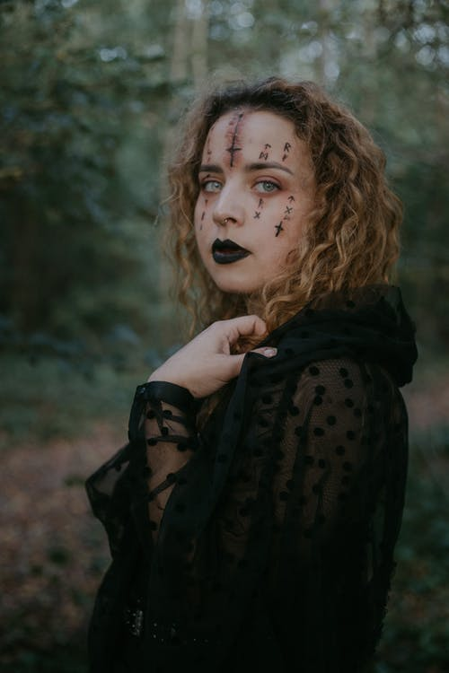 Woman with scary makeup in forest
