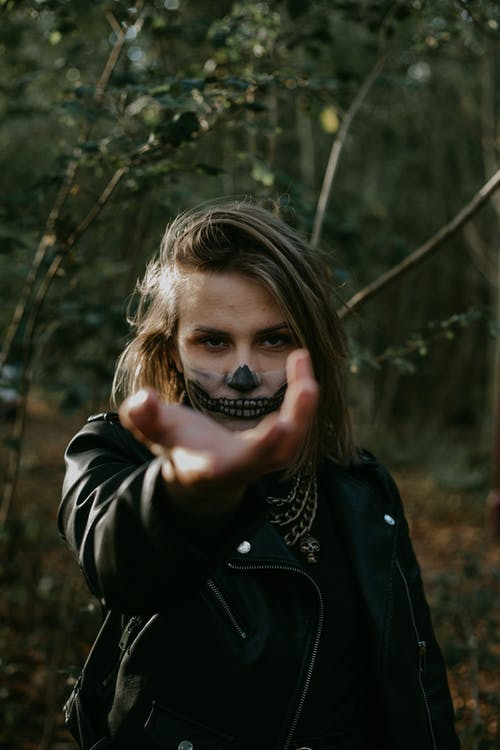 Serious woman with Halloween makeup in forest
