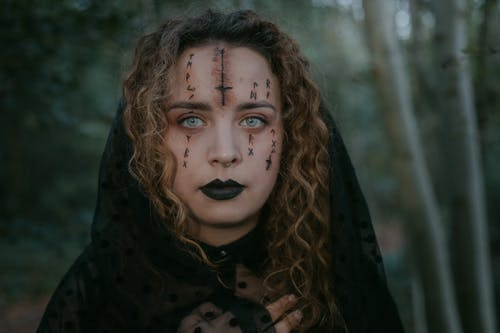 Portrait of female with spooky face art in black veil standing in forest and looking at camera