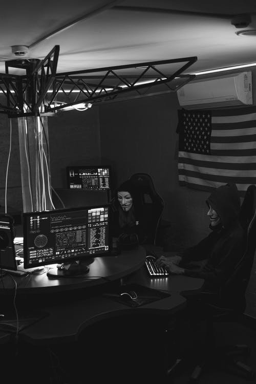Grayscale Photo of Hackers Sitting on Chairs