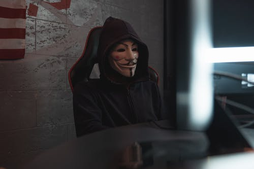 Person in Black Hoodie Hacking a Computer System