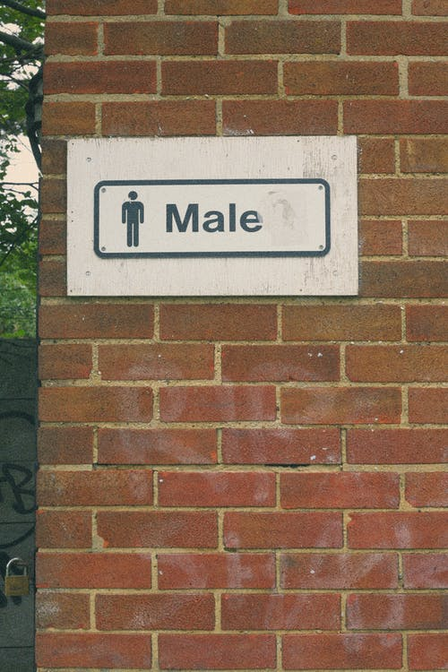 A Male Restroom Sign on Brick Wall