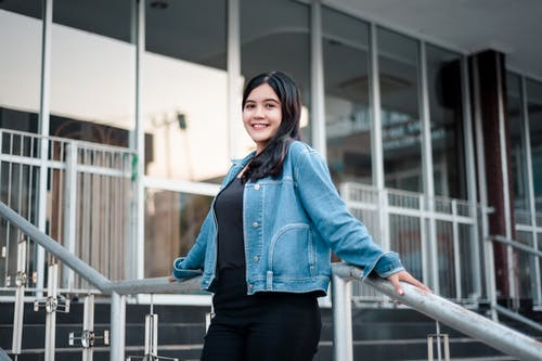Woman in Blue Denim Jacket and Black Pants Leaning against a Handrail