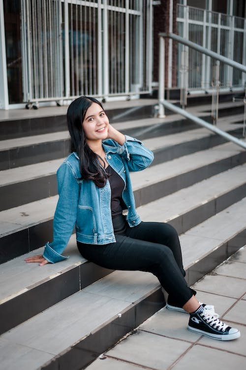 Woman in Blue Denim Jacket and Black Pants Sitting on Concrete Stairs