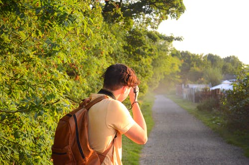 Back View of a Man in Brown Backpack Standing on Road Taking Pictures