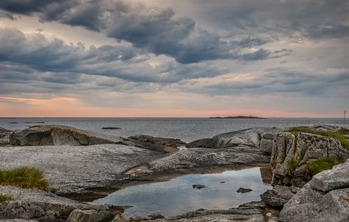 Rocky coast near endless sea under cloudy sky at sunset