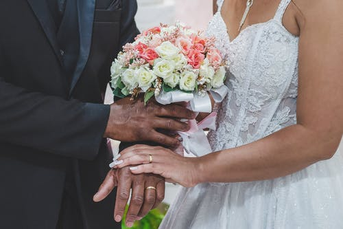 Woman in White Floral Wedding Dress Holding Man in Black Suit