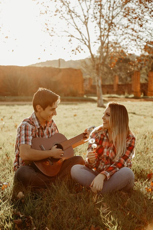 Happy couple in field with guitar