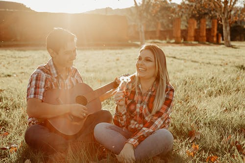 Happy young couple sitting on grass and playing acoustic guitar while spending time together