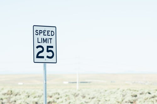 White sign on roadside with speed limit against empty green field at daytime
