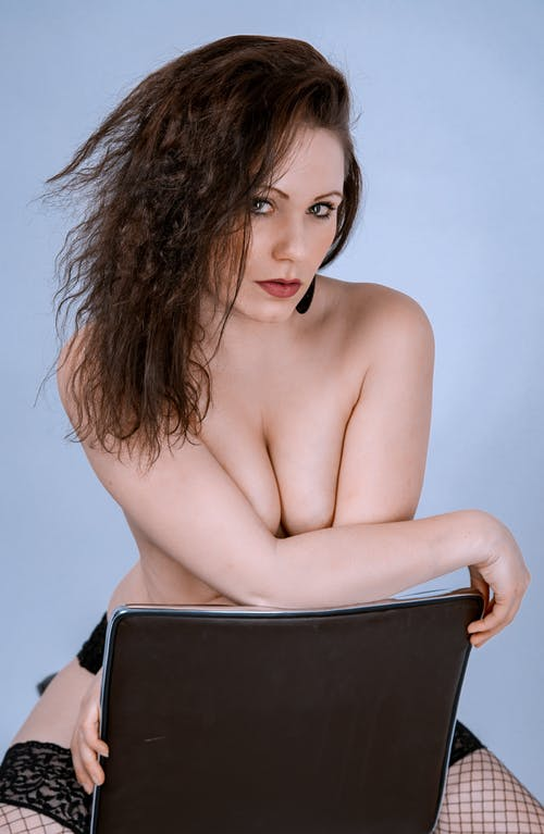 Topless Woman Sitting on Black Chair
