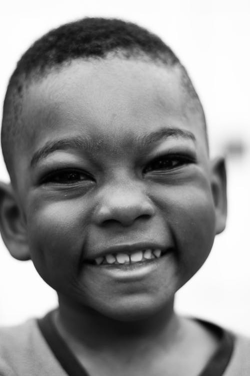 Black and white of African American little boy with short hair looking at camera with toothy smile in daylight