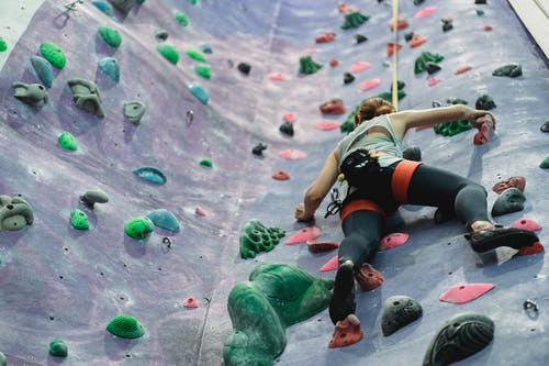 From below of anonymous female equipped with safety rope and harness moving up at rock climbing wall at gym