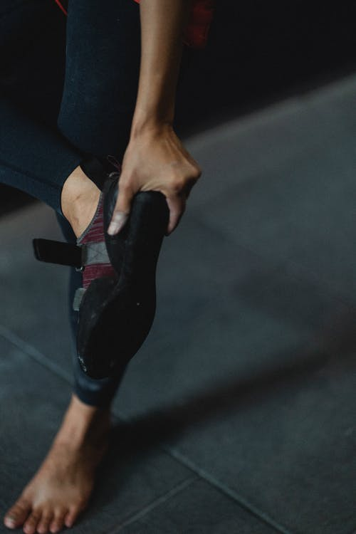 Anonymous person in sports leggings standing with raised leg and taking off shoes