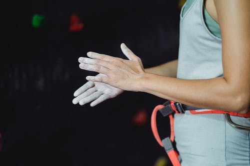 Side view of anonymous lady in equipment chalking hands before climbing against climbing wall