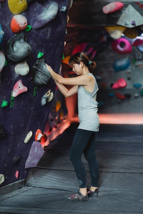 Strong ethnic female athlete preparing for bouldering training