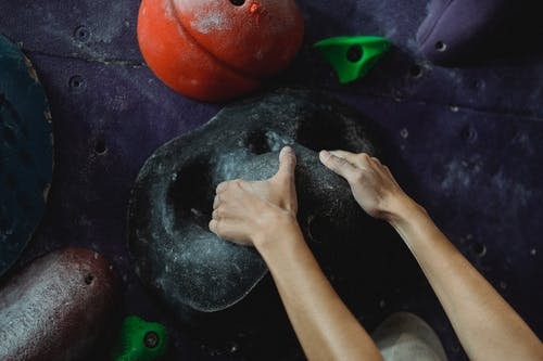 Crop anonymous female mountaineer practicing endurance and strength on climbing wall in bouldering center