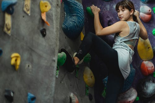 Focused ethnic sportswoman climbing on wall with grips