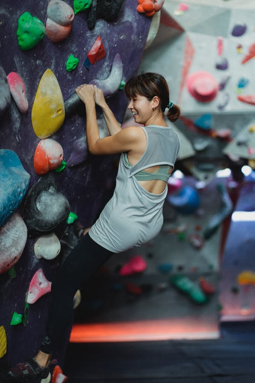Full body back view of cheerful female alpinist climbing high on wall during active extreme training in gym