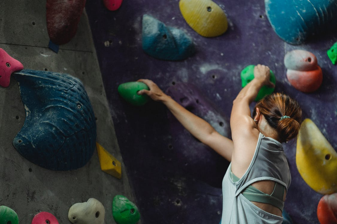 Faceless muscular sweaty female climber climbing high on wall during bouldering training in sports center