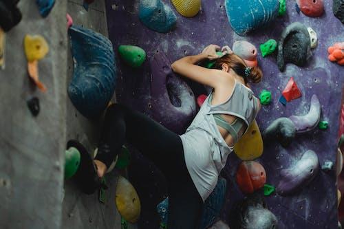 Climber in activewear exercising on climbing wall