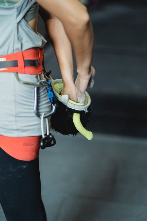 Side view of crop anonymous female alpinist wearing sportswear and safety harness while putting hands in chalk