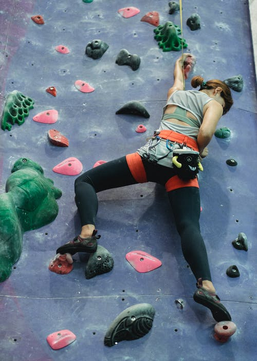 Woman hanging on rope on climbing wall
