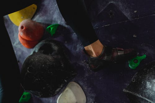 Strong female climber climbing on wall in gym
