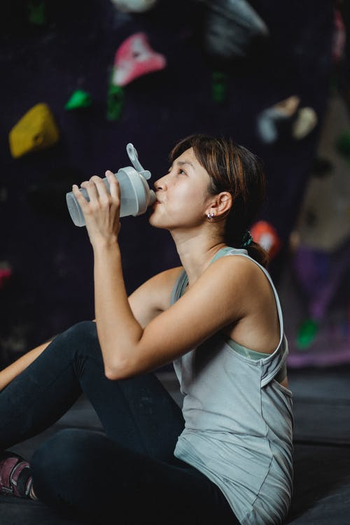 Side view of tired Asian female climber refreshing with water after exercising on climbing wall