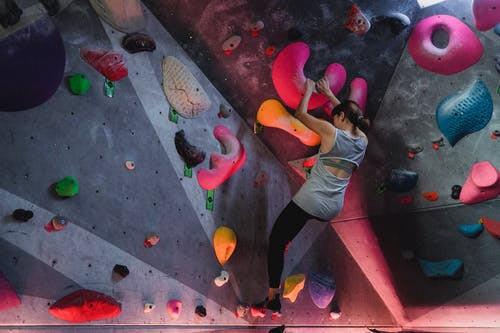 Strong alpinist climbing high on wall