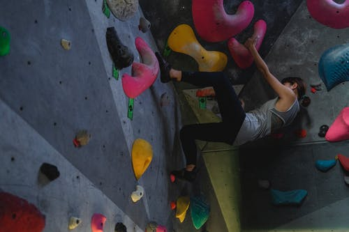 Strong climber during powerful boulder training in gym
