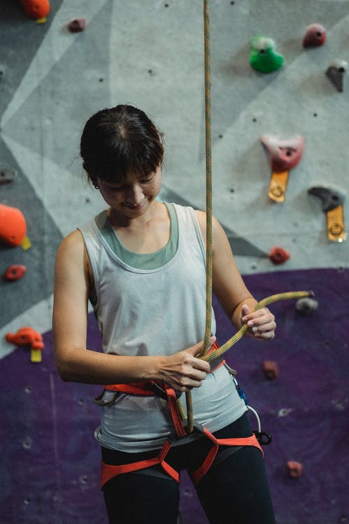 Positive Asian female alpinist tying rope for safe training on climbing wall in bouldering club