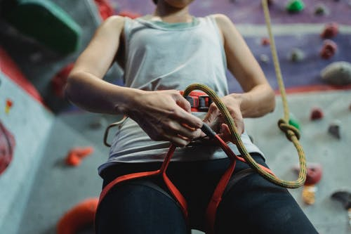 From below of crop anonymous female climber putting on cable of belay during preparation for climbing training