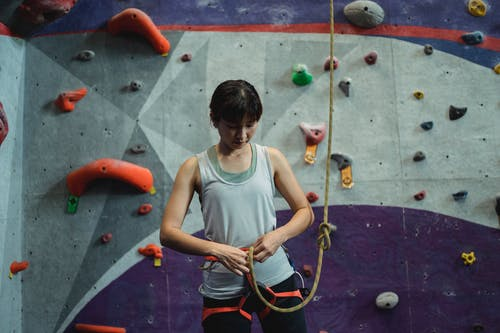 Serious Asian woman fastening safety harness and rope for climbing on wall in bouldering center