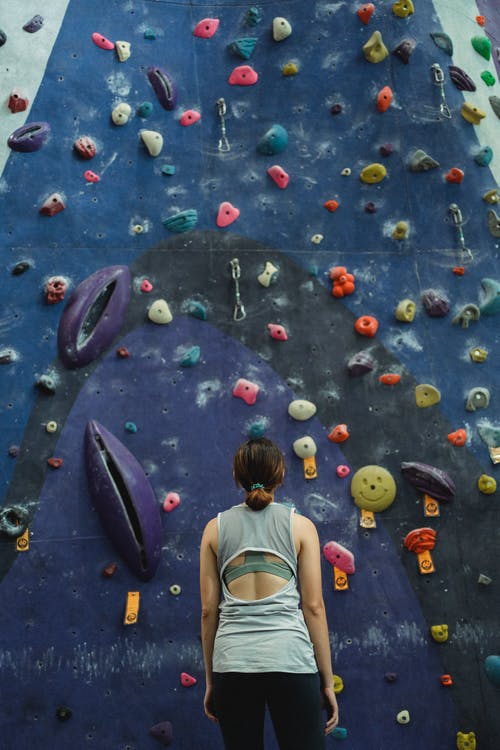 Woman preparing for climbing high on wall