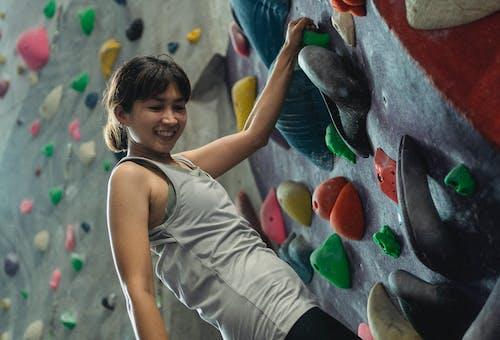 Smiling Asian woman climbing wall in modern gym